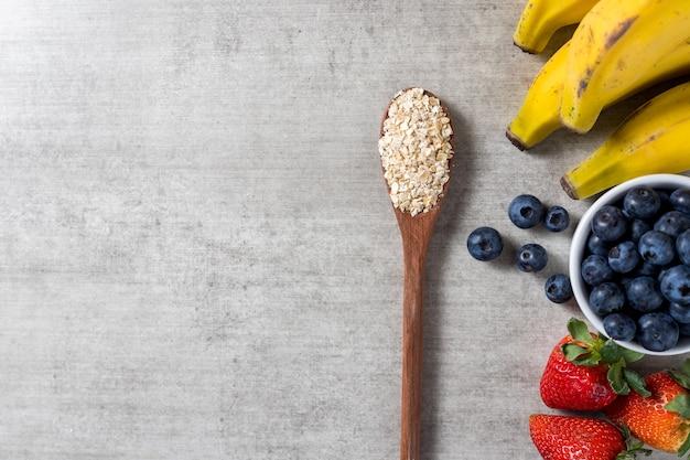 Tło z łyżką pełną owsa i kilka świeżych zdrowych owoców na drewnianym stole. banany, jagody i truskawki. widok z góry. skopiuj miejsce.