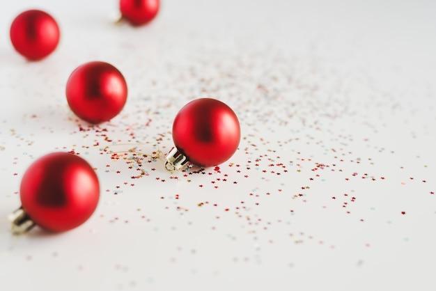 Tło z małych czerwonych bombek i kolorowych błyskotek na białym tle