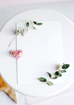 Tło z miejsca kopiowania puste na białym stole z brokatem serca, gałęzi eukaliptusa, kwiatów i liści. widok z góry na białą księgę, płaski, minimalistyczny styl. makijaż karty.