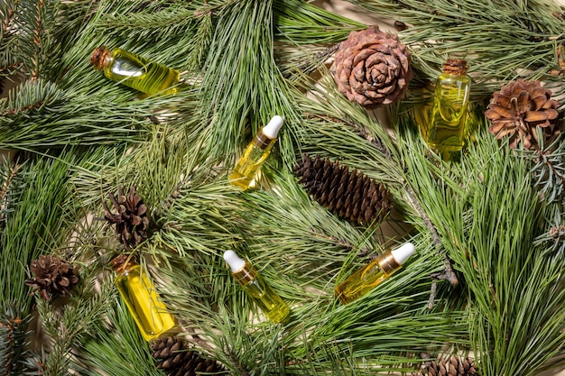 Tło z naturalnych świeżych zielonych gałęzi i szyszek sosny, świerku i cedru oraz małych szklanych butelek z aromatycznymi olejkami eterycznymi iglastymi spa. świąteczna koncepcja aromaterapii i spa. widok z góry.