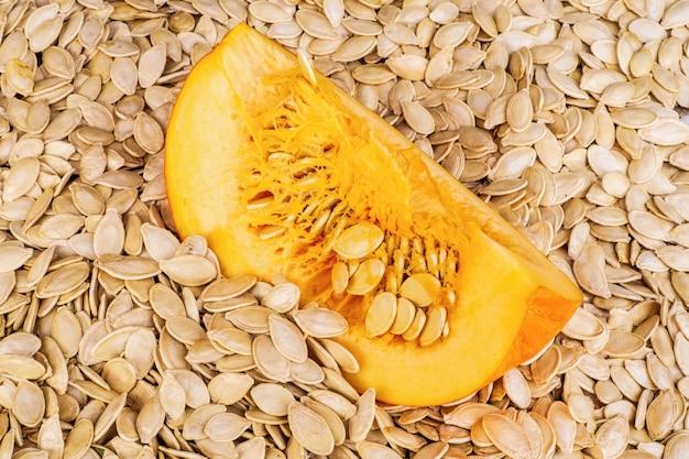 Tło z pestek dyni i pokrojonej dyni po wysuszeniu na żywność lub olej kuchenny