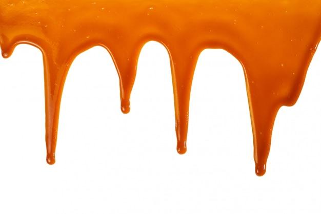 Tło z przepływającym sosem karmelowym na białym tle
