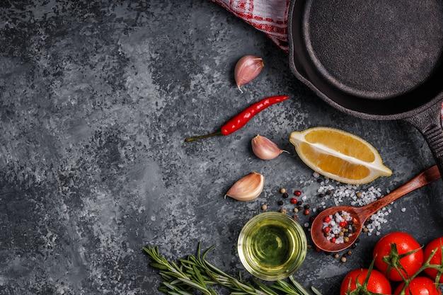 Tło z przyprawami, ziołami, oliwą z oliwek i patelni do gotowania.