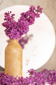 Tło z pustej przestrzeni kopii na stole z fioletowym kwiatem bzu. fioletowe kwiaty. widok z góry na białą księgę, płaski, minimalistyczny styl. makijaż karty.