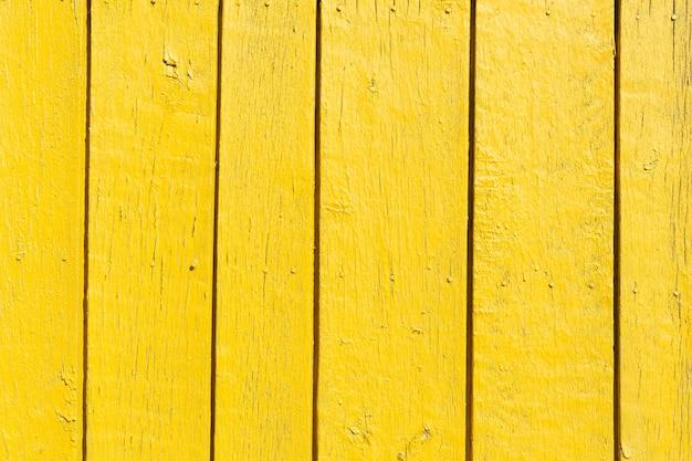 Tło z rocznika teksturowanej żółtej drewnianej ścianie z szorstkiej powierzchni wyblakły