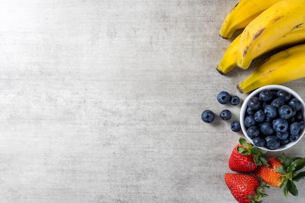 Tło z świeżych zdrowych owoców na drewnianym stole. banany, jagody i truskawki. widok z góry. skopiuj miejsce.