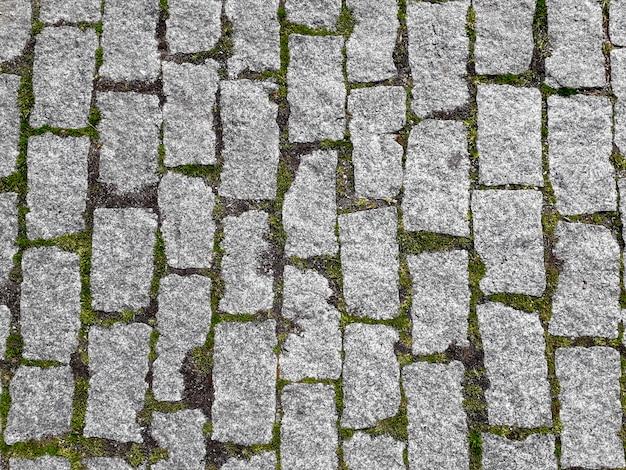 Tło z szarej kostki brukowej i trawy między nimi
