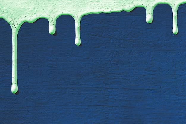 Tło z teksturą betonowej ściany stiukowej w kolorze niebieskim, na którą spływa farba w kolorze miętowym.
