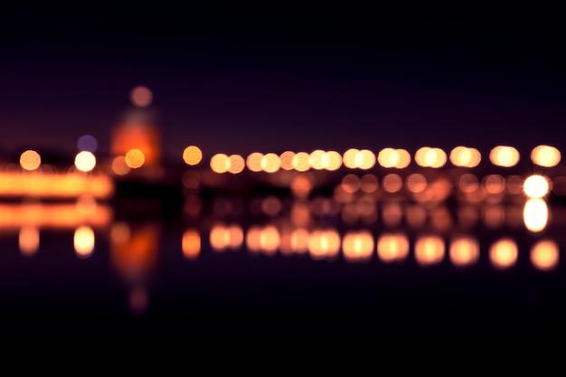 Tło z zamazanymi światłami lampiony przy nocą. niesamowite odbicie bokeh w rive. tuluza, francja
