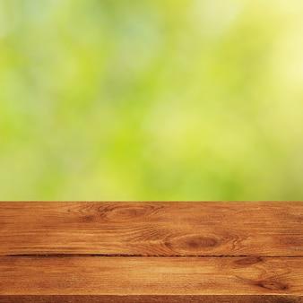 Tło z zamazanymi zielonymi liśćmi i pustymi drewnianymi deskami na pierwszym planie. do prezentacji produktów, wolna przestrzeń, układ, makieta, tablica perspektywiczna, tablica tła.