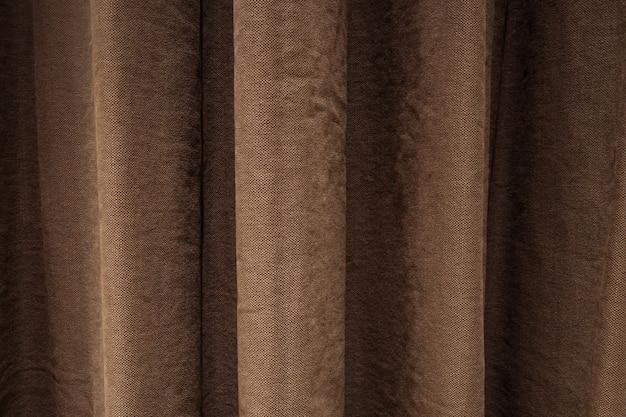 Tło z zasłoną w kolorze brązowym wiszącą i tworzącą draperię