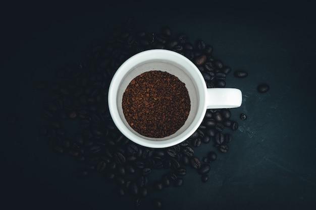 Tło z ziaren kawy i filiżankę z surowej kawy, widok z góry