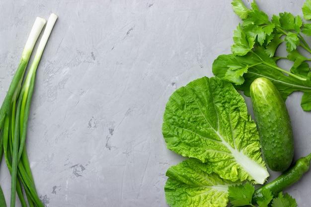 Tło z zielonymi warzywami, sałatką, ogórkiem, zieloną cebulą i cukinią na szarym kamiennym blacie