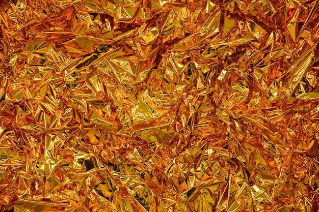 Tło z złotej folii z błyszczącą pogniecioną powierzchnią dla tekstury tła