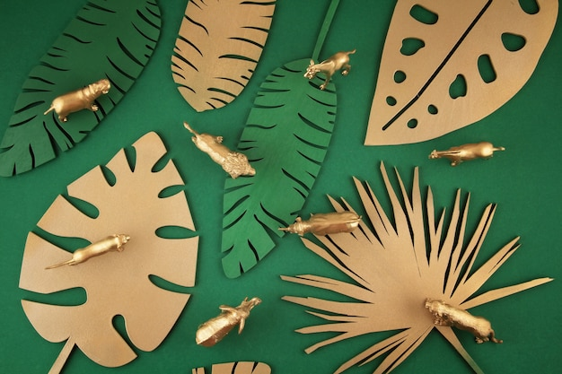 Tło z złotymi tropikalnymi liśćmi i egzotycznymi zwierzętami