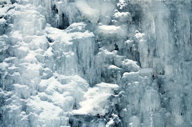 Tło zamarzniętego górskiego wodospadu. zimowy krajobraz, zimne cienie, skały pokryte śniegiem i lodem