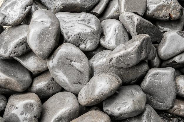 Tło zaokrąglone szare kamienie. tekstura naturalne mokre kamienie