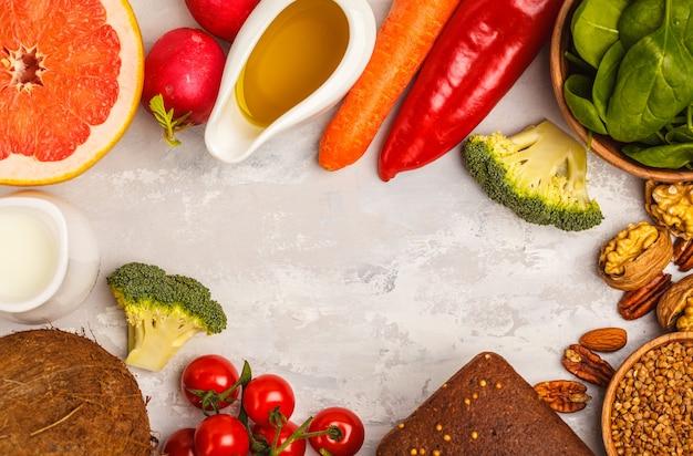 Tło zdrowej żywności, modne produkty diety alkalicznej - owoce, warzywa, zboża, orzechy, olej, białe tło, miejsce