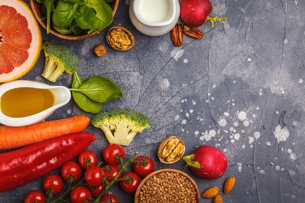 Tło zdrowej żywności, modne produkty diety alkalicznej - owoce, warzywa, zboża, orzechy, olej, ciemne tło, widok z góry