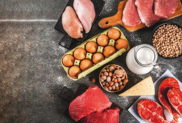 Tło zdrowej żywności. wybór źródeł białka: mięso wołowe i wieprzowe, filet z kurczaka, łosoś, jajko, fasola, orzechy, mleko. widok z góry copyspace, ciemne tło