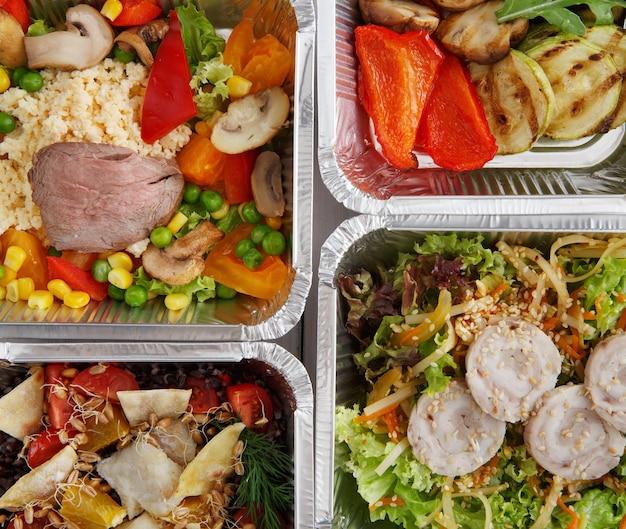 Tło zdrowej żywności. zabierz naturalną żywność organiczną w foliowych pudełkach. sałatki mięsno-warzywne. widok z góry, płaski układ.