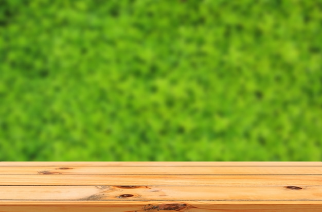 Tło zielonych liści z gładkim drewnianym stołem produktowym