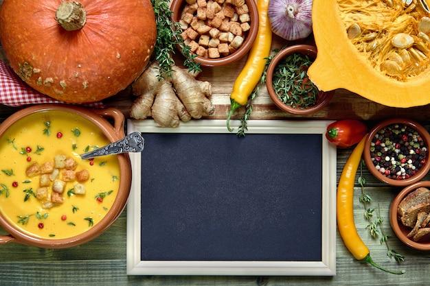 Tło zupa dyniowa z pustą tablicą obok miski zupy i zdrowych składników zupy