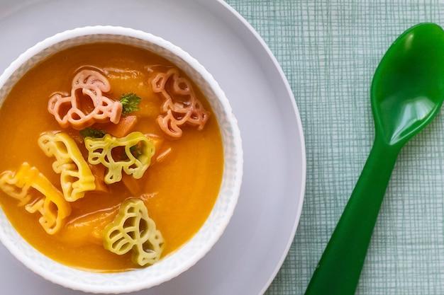 Tło zupy marchewkowej, zwierzęta makaronowe, zdrowa żywność dla dzieci tapeta