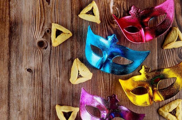 Tło żydowskiego święta z ciasteczkami hamantaschen i maską karnawałową na purim. skopiuj miejsce.