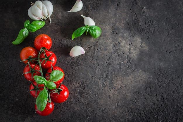 Tło żywności. organiczne pomidory czereśniowe z bazylią i czosnkiem