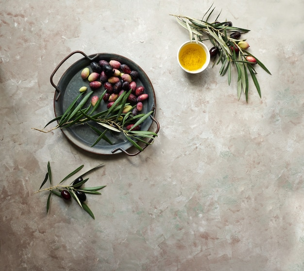 Tło żywności z gałęzi drzewa oliwnego, serwetka i talerz, sztućce nóż i widelec, oliwa z oliwek na betonowym tle