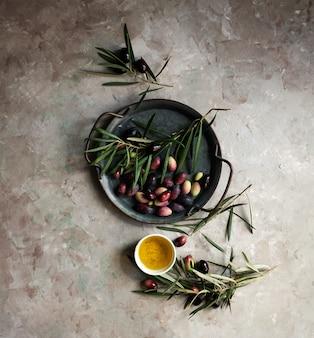 Tło żywności z gałęzi drzewa oliwnego, serwetka i talerz, sztućce nóż i widelec, oliwa z oliwek na ścianie betonowej