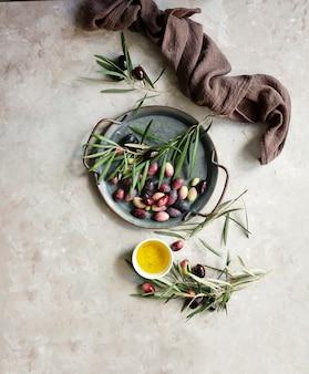 Tło żywności z gałęzi drzewa oliwnego, serwetka i talerz, sztućce noża i widelca, oliwa z oliwek