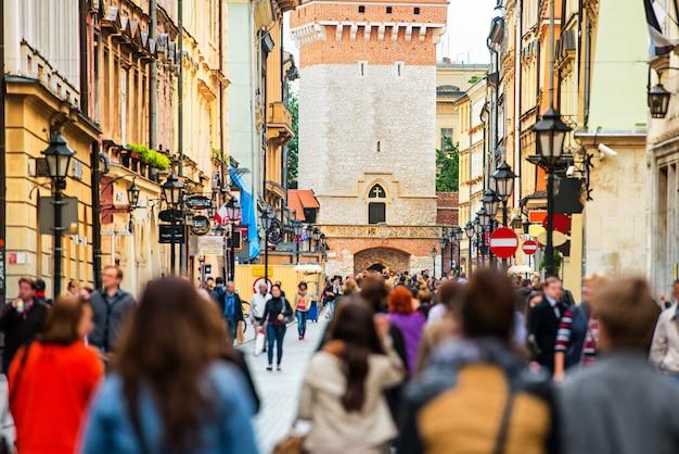 Tłum anonimowych ludzi spacerujący po ruchliwej ulicy. kraków, stare miasto, polska.
