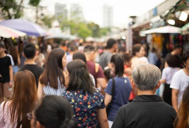 Tłum anonimowych ludzi spacerujących i robiących zakupy na targu weekendowym.