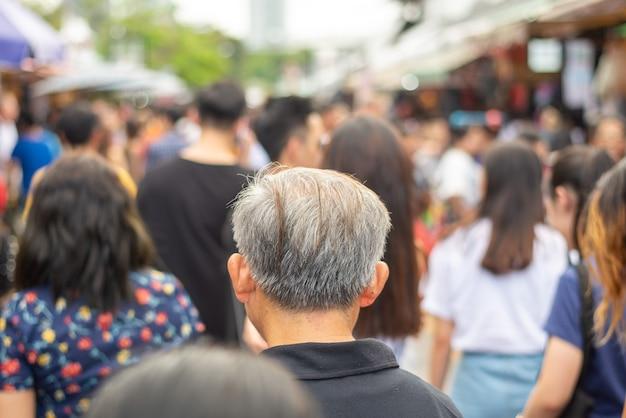 Tłum anonimowych ludzi spacerujących i robiących zakupy na weekendowym targu jatujak market w bangkoku w tajlandii.