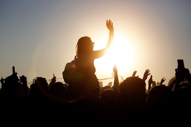 Tłum cieszy się letnim festiwalem muzycznym, zachodem słońca, czarnymi sylwetkami, rękami w górze, dziewczyną w centrum