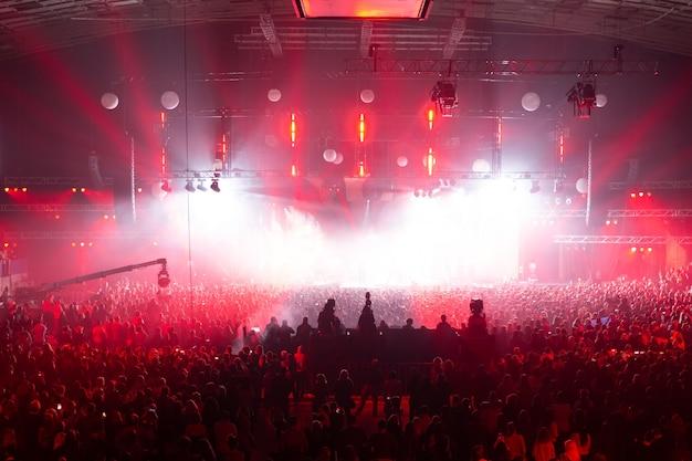 Tłum koncertowy bawiący się na koncercie rockowym. duża sala koncertowa z dużą sceną. dużo ludzi. sprzęt odgromowy. telewizja kręci koncert kilkoma kamerami.
