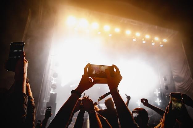 Tłum ludzi bawiących się podczas oglądania programu koncertowego na festiwalu muzycznym. podniesione ręce z telefonami komórkowymi.