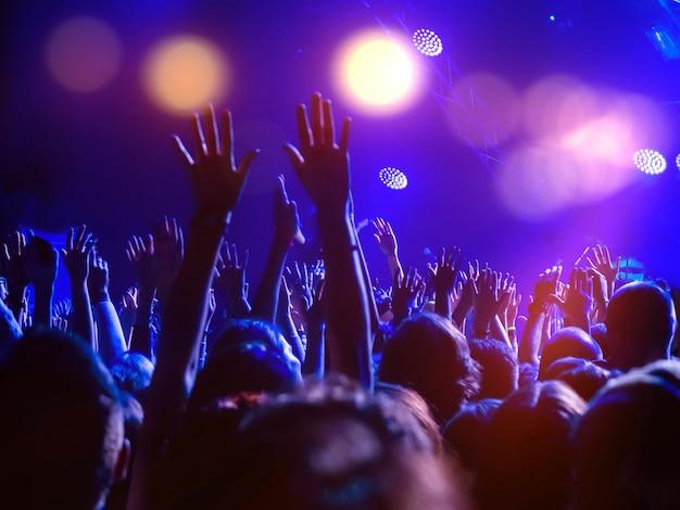 Tłum ludzi na parkiecie z podniesionymi rękami i światłami dyskotekowymi