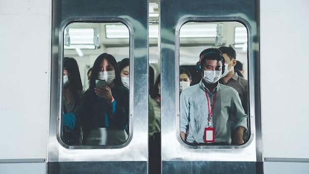 Tłum ludzi noszących maskę na zatłoczonym publicznym metrze podróży