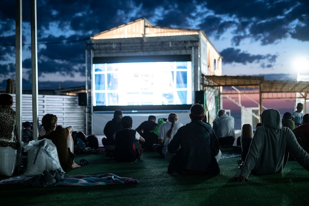 Tłum ludzi oglądający nocą film w kinie na świeżym powietrzu