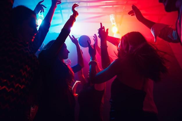Tłum ludzi w sylwetce podnosi ręce na parkiecie na neonowym tle. życie nocne, klub, muzyka, taniec, ruch, młodzież. fioletowo-różowe kolory i poruszające dziewczyny i chłopcy.