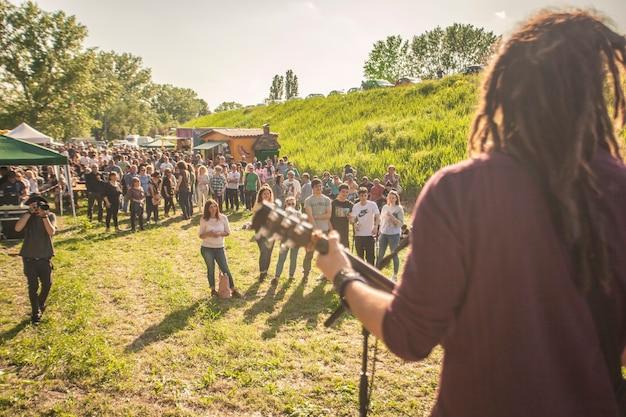 Tłum na koncercie rockowym na świeżym powietrzu o zachodzie słońca