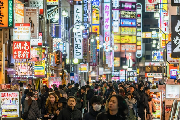 Tłum niezdefiniowani ludzie chodzi wokoło nocnej ulicy ulicy przy kabukicho shinjuku stacja