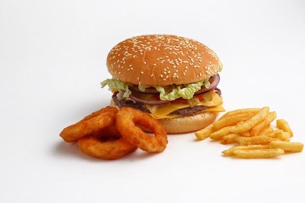 Tłumacz hamburger z krążkami cebuli i frytkami leży na drewnianym podłożu