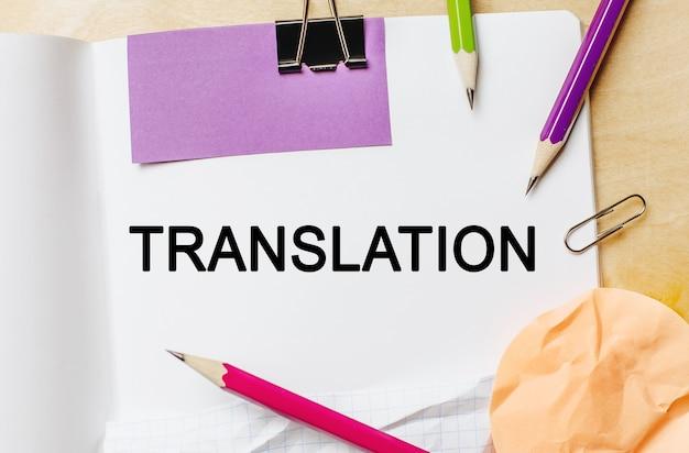 Tłumaczenie tekstu na białym miejscu z ołówkami, naklejkami i spinaczami
