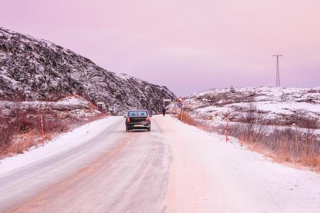 Tłumaczenie znaku drogowego: wieś teriberka. samochód jedzie autostradą między arktycznymi wzgórzami. stara wioska rybacka na brzegu morza barentsa, półwysep kolski, teriberka, rosja.