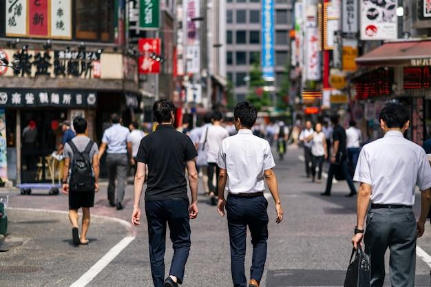 Tłumy przechodzą przez kabukicho w dzielnicy shinjuku, miejscu rozrywki i czerwonych latarni.