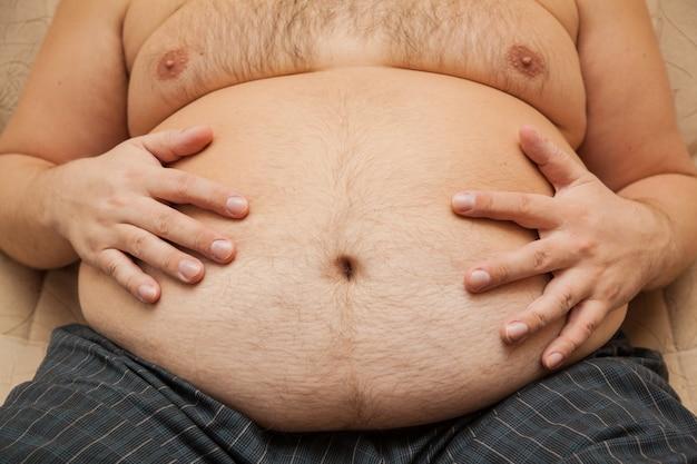 Tłusty brzuch otyłego mężczyzny. konsekwencje niedożywienia